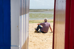 Man on the beach in front of beach huts Stock Photo