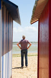 Man on the beach in front of beach huts Royalty Free Stock Photography