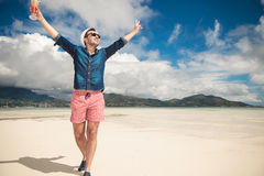 Man on the beach holding both hands in the air Stock Photo