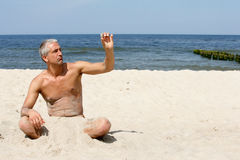Man on the beach holding stone Royalty Free Stock Photo