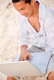 Man at the beach with laptop Stock Photo