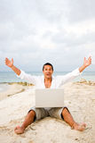 Man on beach with laptop Stock Photos