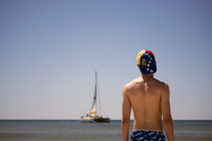 Man on beach looking at sailboat Stock Photos