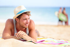 Man on beach lying in sand looking to side. Smiling happy wearing hipster summer hat. Young male model enjoying summer travel holiday by the ocean Royalty Free Stock Images
