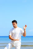 Man on the beach meditating Stock Photos