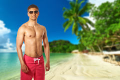 Man on beach with palm tree at Seychelles Royalty Free Stock Images