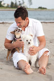 Man on beach with pet dogs. Handsome barefoot man on beach with two cute pet dogs Royalty Free Stock Image