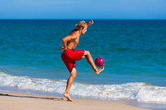 Man on beach playing soccer Royalty Free Stock Photo