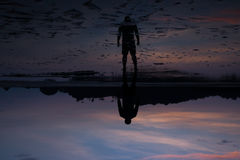 Man on the beach with reflection in water during sunset. Royalty Free Stock Image