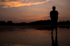 Man on the beach with reflection in water during sunset. Royalty Free Stock Photos