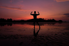 Man on the beach with reflection in water during sunset. Royalty Free Stock Images