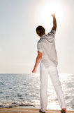 Man at the beach rising the hand Royalty Free Stock Image