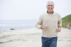 Man at the beach running and smiling Royalty Free Stock Images