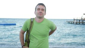 Man on the beach shows a green backpack and smiles at the camera. He turns and shows the bag. stock footage