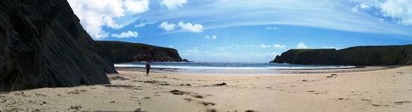 Man on the beach. Sunny panoramic view of Malin Beg beach, Ireland with the man walking Stock Photo