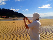 Man On Beach Taking Picture with Phone Royalty Free Stock Photo