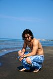 Man on the beach thinking. Fashion model male on the beach relaxing and thinking Royalty Free Stock Photos