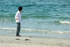 Man on beach throwing rocks into ocean. A white male is standing on the beach throwing rocks into the sea at the gulf of mexico in florida, wearing jeans Stock Photos