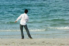 Man on beach throwing rocks into sea Royalty Free Stock Image
