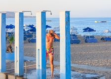 Man on the beach under the shower. Rhodes Island Stock Image