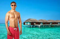 Man on beach with water bungalows Stock Photos