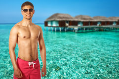 Man on beach with water bungalows Royalty Free Stock Image