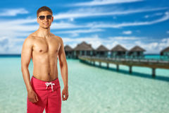 Man on beach with water bungalows Stock Photo