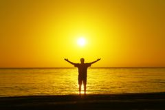 A man on the beach welcomes the sunrise. Hands are spread apart. stock images