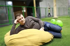 Man on bean bag chair. Man resting on bean bag chair indoor royalty free stock images