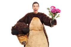 Man in a bear costume holding a bouquet of flower Royalty Free Stock Photography