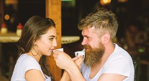 Man with beard and attractive happy smiling girl drinking coffee. Couple in love drink black espresso coffee in cafe. Couple happy spend time in cafe. Share royalty free stock photos