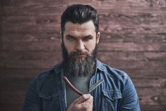 Man with beard. Bearded man is holding an old fashioned razor and looking seriously at camera, on wooden background royalty free stock photos