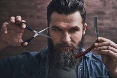 Man with beard. Bearded man is holding razor and scissors and looking at camera, on a wooden background stock image
