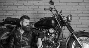 Man with beard, biker in leather jacket near motor bike in garage, brick wall background. Bikers lifestyle concept. Hipster, brutal biker on pensive face in royalty free stock photography