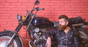 Man with beard, biker in leather jacket near motor bike in garage, brick wall background. Bikers lifestyle concept. Hipster, brutal biker on pensive face in royalty free stock photos