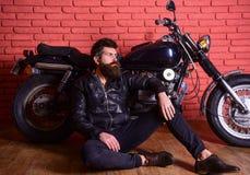Man with beard, biker in leather jacket near motor bike in garage, brick wall background. Hipster, brutal biker on. Pensive face in leather jacket sit on floor stock image