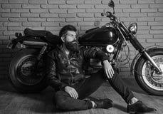 Man with beard, biker in leather jacket near motor bike in garage, brick wall background. Hipster, brutal biker on. Pensive face in leather jacket sit on floor stock photos
