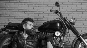 Man with beard, biker in leather jacket near motor bike in garage, brick wall background. Hipster, brutal biker on. Pensive face in leather jacket sits, leans royalty free stock photo