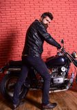 Man with beard, biker in leather jacket near motor bike in garage, brick wall background. Hipster, brutal biker on. Serious face in leather jacket sits down on royalty free stock images