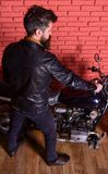 Man with beard, biker in leather jacket near motor bike in garage, brick wall background. Masculine hobby concept. Hipster, brutal biker in leather jacket sits royalty free stock photos