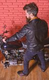 Man with beard, biker in leather jacket near motor bike in garage, brick wall background. Masculine hobby concept. Hipster, brutal biker in leather jacket sits stock image