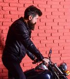 Man with beard, biker in leather jacket near motor bike in garage, brick wall background. Start of journey concept. Hipster, brutal biker on serious face in stock photography