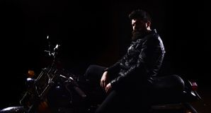 Man with beard, biker in leather jacket sitting on motor bike in darkness, black background. Macho, brutal biker in. Leather jacket riding motorcycle at night Royalty Free Stock Image