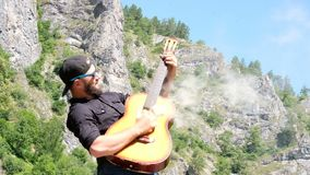 A guy with a beard in a black shirt and sunglasses pretends to play a smoky acoustic guitar. Strange funny video for a music video. A man with a beard in a black stock footage