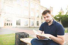 Man with a beard and a black T-shirt sitting on a bench on the background of architecture and reading a book. Portrait of a beautiful man with a beard and a royalty free stock images