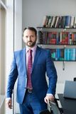 Man with beard in blue formal suit. Businessman or director pose at workplace. Business, entrepreneurship concept. Fashion, style, dress code. Career Royalty Free Stock Images