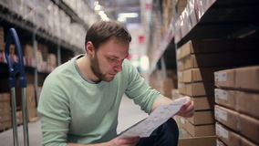 A man with a beard in a blue sweater checking his list in a warehouse stock video footage