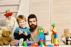 Man with beard and boy play on wood wall background. Family and childhood concept. Father and son with smiling faces create colorful constructions with toy royalty free stock images