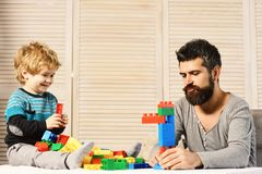 Man with beard and boy play on wooden wall background. Man with beard and boy play together on wooden wall background. Father and son with happy faces play with royalty free stock photography