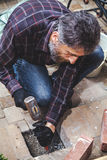 Man with beard breaks masonry hammer and chisel Royalty Free Stock Photos